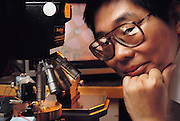Micro Technology: Tai Yu-Chong of U. C. Berkeley with a synchronous micromotor under a video microscope. Model Released.[1989]