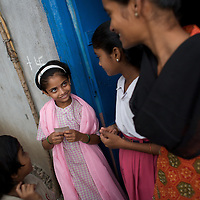 """At home, Vasanti smiles to daughter Shruda, 10. Both are HIV positive. Vasanti Shinde, 26, works for the Save Foundation. <br /> <br /> Like many of the women who work for and with UNDP partners the Save Foundation, Vasanti Shinde, age 26, only found out that she was HIV positive after her husband became seriously ill with an AIDS-related illness five years ago. Vasanti's husband subsequently died. Vasanti now lives with her two younger daughters Shrudha, age 10, and Vrinda, 8, in the one-room home of her brother in Sangli city. Vasanti's elder daughter, eleven year old Shubhada is being brought up by her paternal grandmother and sees her mother during holidays. Vasanti knows that Shubhada is HIV negative and Shruda is positive but anxiety over the result means that she refuses to have Vrinda tested for HIV. For a monthly income of Rs.3500, Vasanti works as a field officer and counselor for the Save Foundation. She works in the positive-people's pharmacy for no pay. Her work with the Save Foundation entitles her access to a credit union which provides low interest loans covering medical expenses. Though first-line drugs and homeopathic medicine keep Vasanti healthy, she is prone to infection and recently suffered a bout of influenza. Vasanti is completely open about her HIV status and most of her neighbours know that she is HIV positive. Vasanti says that """"I used to feel like I was going to die. Now, because of the Save Foundation, I feel like I'm going to live."""" <br /> <br /> Photo: Tom Pietrasik<br /> Sangli, Maharashtra. India<br /> August 28th 2008"""