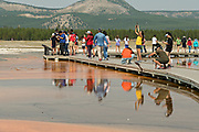 Tourists walk along the boardwalk at Grand Prismatic Spring the largest hot spring in Yellowstone National Park and third largest in the world. Grand Prismatic is about 250 by 300 feet in size, averages 160 degrees Fahrenheit and is up to 160 feet deep. The bright colors around the spring are from cyanobacteria mats. The Grand Prismatic Spring is part of the Midway Geyser Basin Excelsior Group in Yellowstone, Wyoming.