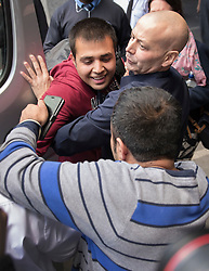 © Licensed to London News Pictures. 17/10/2016. Croydon, UK. 16 year old Afghanistani refugee 'Haris' is held back by an immigration official (top) as he tries to reach out to his uncle Jan Ghazi, as the first children from the Calais jungle refugee camp leave the Home Office immigration centre in Croydon. British authorities are bringing over about 100 children this week to be reunited with their relatives. The French government have announced that they will be dismantling the camp this month. credit: Peter Macdiarmid/LNP