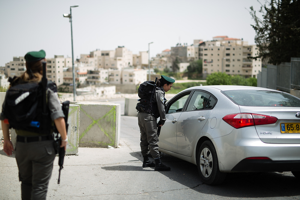 Israeli Border Police Woman Corporal Mor Hadad (R) inspects vehicles at the exit of the East Jerusalem neighborhood of Issawiya as Staff Sergeant Chen Cohen (L) stands guard, in Jerusalem, Israel, on April 10, 2016.