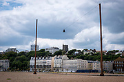 'Out of Tune' by AK Dolven, a sound installation on the 21st of May 2020 on the seafront in Folkestone, United Kingdom. Originally commissioned for the Folkestone Triennial Art festival, A K Dolven's installation 'Out of Tune' features a sixteenth century tenor bell from Scraptoft Church in Leicestershire, which had been removed for not being in tune with the others. It is suspended from a steel cable strung between two 20m high steel beams, placed 30m apart. The bell was cast by Hugh Watts in the seventeenth century in Leicester. The Watts family were the leading bell founders in that city in the early 17th century. In all, they were responsible for almost two hundred castings for churches in the county. Hugh Watts prospered and was the Mayor of Leicester when King Charles 1st visited the city in 1634.