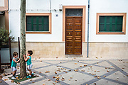 Esporles, Mallorca, Two boys dressed in green play around a house with the green shutters 04-08-2018