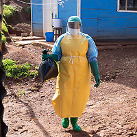 At a clinic supported by IMA, a nurse in full PPE disposes of clinical waste using the Ebola protocols. The waste is destroyed in an incinerator built with support by IMA.