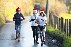 ©Licensed to London News Pictures 23/12/2019. <br /> Eynsford ,UK. Runners with santa hats on keeping fit this morning. The River Darent water levels have continued to rise this morning causing flooding to parts of Eynsford Village in Kent. Photo credit: Grant Falvey/LNP