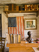"""Montana's oldest standing public school, used in the town of Twin Bridges from 1867-1873, is now preserved at Nevada City, Montana, USA. The wooden classroom contains a desk, books, and an American flag with 48 stars. Nevada City was a booming placer gold mining camp from 1863-1876, but quickly declined into a virtual ghost town. This fascinating town inspires you to imagination what life must have been like in early Montana when gold was discovered at nearby Alder Gulch. More than 90 buildings from across Montana have been gathered for preservation at Nevada City, mostly owned by the people of the State of Montana, and managed by the Montana Heritage Commission. In 2001, the excellent PBS television series """"Frontier House"""" used one of the buildings and its furnishings to train families in re-creating pioneer life. A miner's court trial and hanging of George Ives in the main street of Nevada City was the catalyst for forming the Vigilantes, a group of citizens famous for taking justice into their own hands in 1863-1864. Directions: go 27 miles southeast of Twin Bridges, Montana on Highway 287."""