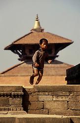 KATHMANDU, NEPAL - OCTOBER 1992 - A young boy plays infront of a temple in Kathmandu. <br />(PHOTO © JOCK FISTICK)