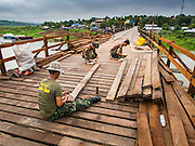 16 SEPTEMBER 2014 - SANGKHLA BURI, KANCHANABURI, THAILAND: Soldiers in the Royal Thai Army and Mon civilians from the Mon community in Sangkhla Buri work on the deck of the Mon Bridge. The 2800 foot long (850 meters) Saphan Mon (Mon Bridge) spans the Song Kalia River. It is reportedly second longest wooden bridge in the world. The bridge was severely damaged during heavy rainfall in July 2013 when its 230 foot middle section  (70 meters) collapsed during flooding. Officially known as Uttamanusorn Bridge, the bridge has been used by people in Sangkhla Buri (also known as Sangkhlaburi) for 20 years. The bridge was was conceived by Luang Pho Uttama, the late abbot of of Wat Wang Wiwekaram, and was built by hand by Mon refugees from Myanmar (then Burma). The wooden bridge is one of the leading tourist attractions in Kanchanaburi province. The loss of the bridge has hurt the economy of the Mon community opposite Sangkhla Buri. The repair has taken far longer than expected. Thai Prime Minister General Prayuth Chan-ocha ordered an engineer unit of the Royal Thai Army to help the local Mon population repair the bridge. Local people said they hope the bridge is repaired by the end November, which is when the tourist season starts.    PHOTO BY JACK KURTZ
