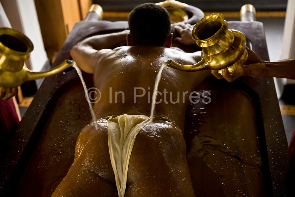 A patient has warm water poured over his body after having completed a massage with medicated oil as part of the overall Ayurveda experience at Kalari Kovalikom, Kerala, India.