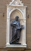 Statue detail on the outside of a church in Florence, Italy. Semi enclosed figurative statues such as this appear all over Florence. This is a statue of St. Peter.
