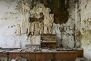 Concert hall with water damaged soviet relief sculpture and piano.