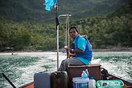 Ko Phangan, Thailand - June 24, 2017: A man driving a long-tail boat departs Bottle Beach off the north coast of Ko Phangan, Thailand.