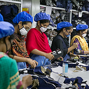 INDIVIDUAL(S) PHOTOGRAPHED: N/A. LOCATION: Universal Menswear Factory, Narayanganj, Bangladesh. CAPTION: Women work at Universal Menswear Ltd in Narayanganj, Bangladesh. They wear facial masks, which protect them from breathing in fabric particles and dust.