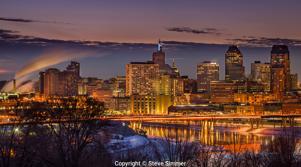 """Downtown St. Paul gives off a beautiful glow. This view from Mounds Park is the only place where you can see the downtowns of St. Paul and Minneapolis in the same frame. And one of the rare occasions when Minneapolis takes a back seat to St. Paul! The First Bank """"1"""" is ice blue this week to recognize the state high school hockey tournaments occurring in St. Paul."""