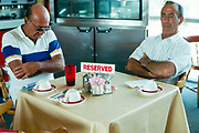 Two men with arms crossed at a restaurant table with a reserved sign on it in Miami, Florida