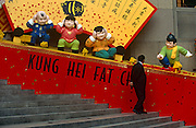 The Chinese words Kung Hei Fat Choi or Happy new Year with cartoon characters outside Bank of China building, Hong Kong.