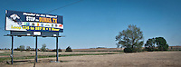 A billboard advertising skiing in Dumas, Texas standing in flat rural west Texas along interstate highway 20 panorama
