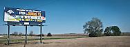 A billboard advertising skiing in Dumas, Texas standing in flat rural west Texas along interstate highway 20 panorama