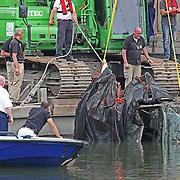 NLD/30-05-2012/MUIDEN - Woensdag 30 mei kwam om 10.00 uur de melding dat tijdens baggerwerkzaamheden in de Singelgracht een auto was aangetroffen met daarin stoffelijke resten. De werkzaamheden werden stilgelegd evenals het scheepvaartverkeer in verband met onderzoek. Toen de auto uit het water was getild bleek het te gaan om de auto van de twee Afgaanse vrouwen uit Naarden en Huizen die sinds 2005 worden vermist. De identiteit van de twee stoffelijke overschotten in de auto moet nog worden vastgesteld. Naar de toedracht van het te water raken van de auto wordt onderzoek gedaan. Het vermoeden is dat er sprake is van een ongeval, andere scenario?s worden echter nog niet uitgesloten...Vermiste Afghaanse vrouwen .Sinds 2005 worden de toen 34-jarige Samina Achakzai uit Huizen en 30-jarige Mari Rahmanzai uit Naarden vermist. De twee vrouwen gingen op 22 maart 2005 na het avondeten vanuit Naarden een stukje rijden om te oefenen met autorijden. Het was de bedoeling dat het een korte ritje zou worden maar de vrouwen keerden nooit naar huis terug...Er is destijds een grootscheepse zoekactie op touw gezet. In eerste instantie werd uitgegaan van een ongeluk maar een misdrijf kon ook niet worden uitgesloten. In 2007 is de zaak tegen het licht gehouden door een Cold Case en Review-team. Naar aanleiding van dit onderzoek is opnieuw gezocht, onder andere met speciale sonarapparatuur, in wateren in de omgeving. De vrouwen en de auto werden echter niet gevonden.