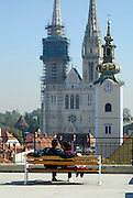Lovers sitting on bench, rooftop view of gilded clock tower of Saint Mary's church and twin spires of Cathedral of the Assumption of the Blessed Virgin Mary and Saint Stephen (Sveti Stjepan) in background. Zagreb, Croatia