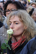 """Protesters woman with white rose to signal support for Charlie Hebdo and Freedom of Press during the massive public rally """"Cry for Freedom"""" takes place in central Paris on Sunday afternoon. The rally brought in people of all colors and creeds from both France and abroad. Many were carrying placards with various slogans. This demonstration happened the weekend after armed gunmen attacked the offices of Charlie Hebdo, killing twelve people, including the editor and celebrated cartoonists; four more are in critical condition. It is the dealiest terror attack in France for over fifty years. Charlie Hebdo is a satirical publication well known for its political cartoons. The jihadists responsible were killed by police in several shootouts on the Friday afternoon.  <br /><br />As a solidarity actions with the deaths at Charlie Hebdo many placards read """"Je suis Charlie"""" translating as """"I am Charlie (Hebdo)"""". Demonstrators held aloft pens, brushes and crayons, symbolizing the profession of journalists and cartoonists who were killed. Many pens were placed in a shrine with candles in the square. Some protesters also refused to ally themselves with Charlie Hebdo."""