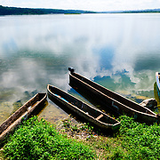 Five traditional wooden boats and canoes beached on the shore of Lake Peten Itza in Flores in northern Guatemala.