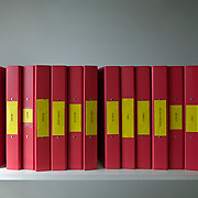 Row of red binders on shelf