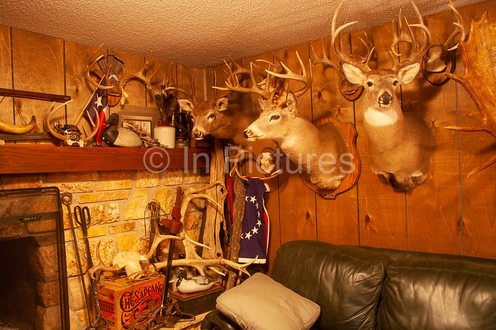 Hunter Byron Grubbs home is full of the guns, trophies, stuffed animals and hunting paraphernalia of an experienced hunter, near Minot, North Dakota, United States. Here, the basement tv room also serves as a museum to his hunters life. Deer, and fish are wall mounted and traps and muskets are all present.