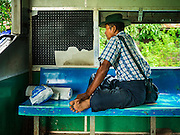 26 OCTOBER 2015 - YANGON, MYANMAR: A man rides the Yangon Circular Train. The Yangon Circular Railway is the local commuter rail network that serves the Yangon metropolitan area. Operated by Myanmar Railways, the 45.9-kilometre (28.5mi) 39-station loop system connects satellite towns and suburban areas to the city. The railway has about 200 coaches, runs 20 times daily and sells 100,000 to 150,000 tickets daily. The loop, which takes about three hours to complete, is a popular for tourists to see a cross section of life in Yangon. The trains run from 3:45 am to 10:15 pm daily. The cost of a ticket for a distance of 15 miles is ten kyats (~nine US cents), and for over 15 miles is twenty kyats (~18 US cents).    PHOTO BY JACK KURTZ