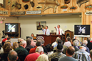 Jim Julia (left) and Dudley Browne auction off Teddy Roosevelt's Fox shotgun.