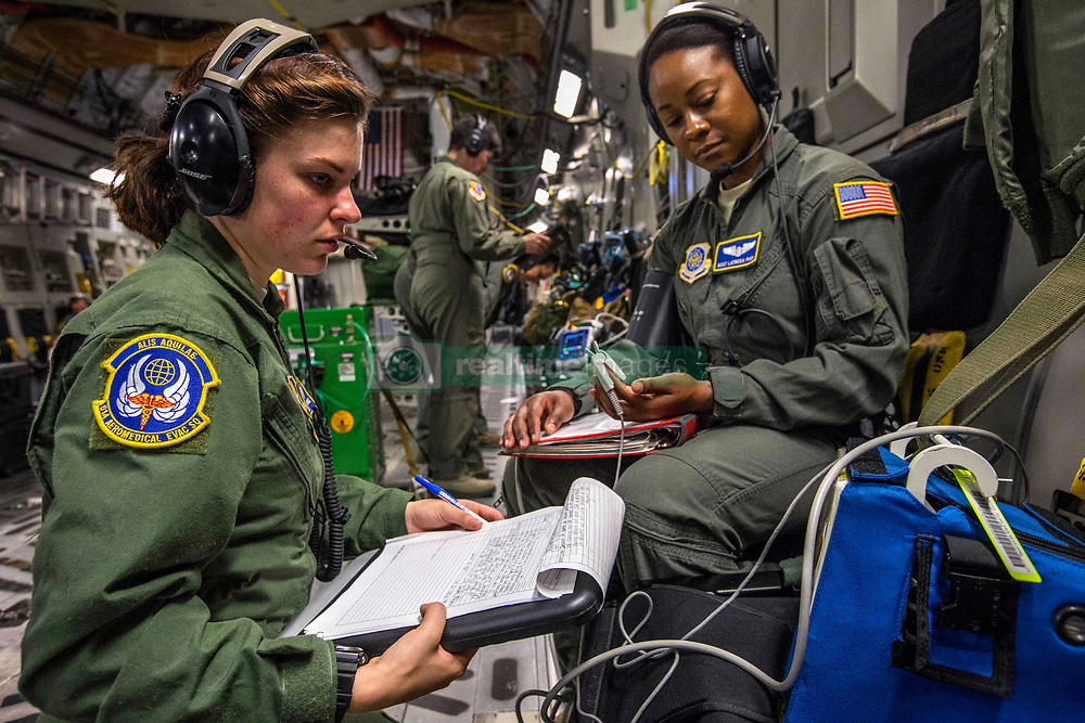 Senior Airman Cristen A. Manjarrez, left, an aeromedical evacuation technician with the 514th Aeromedical Evacuation Squadron, 514th Air Mobility Wing, checks the blood pressure of Master Sgt. Latresia T. Pugh, an aeromedical examiner with Air Mobility Command during a joint training mission with Airmen from the 732nd Airlift Squadron on board a C-17 Globemaster III June 17, 2018. (U.S. Air Force photo by Master Sgt. Mark C. Olsen)