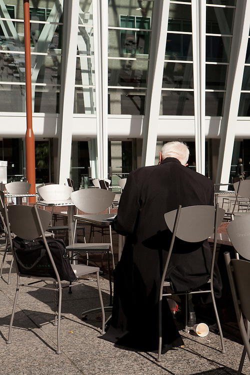 A business man working outdoors in the plaza at Brookfield Place in Toronto's financial district.