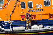 A crew member scecures a buoy to the Royal National Lifeboat Institution RNLI Dover Life boat 17-09 leaving  Folkestone Harbour, Folkestone, Kent. UK.