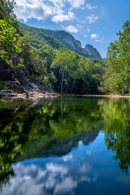 Seneca Rocks is reflected on the waters of the North Fork South Branch of the Potomac river surrounded by lush summer greens and a blue sky.