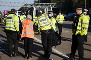 Insulate Britain climate activist Reverend Sue Parfitt is arrested by Surrey Police after blocking the clockwise carriageway of the M25 between Junctions 9 and 10 as part of a campaign intended to push the UK government to make significant legislative change to start lowering emissions on 21st September 2021 in Ockham, United Kingdom. Both carriageways were briefly blocked before being cleared by Surrey Police. The activists are demanding that the government immediately promises both to fully fund and ensure the insulation of all social housing in Britain by 2025 and to produce within four months a legally binding national plan to fully fund and ensure the full low-energy and low-carbon whole-house retrofit, with no externalised costs, of all homes in Britain by 2030.