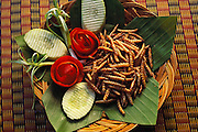 """Fried bamboo larva on a banana leaf with tomato roses, scalloped cucumbers and spring onions. In Thai the larvae are called rot duan, """"express train,"""" because they resemble tiny trains. They taste """"like salty crispy shrimp puffs"""" says Peter Menzel. In the Kan Ron Ban Suan Restaurant, Chiang Mai, Thailand. (Man Eating Bugs: The Art and Science of Eating Insects)"""