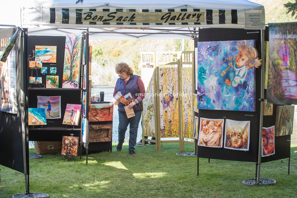 Woman looking at art work during the Thousand Springs Art Festival at Ritter Island near Hagerman, Idaho.