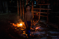 A cambodian kid stands close to a little fire at night. Cambodia, Asia