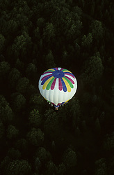 A hot air balloon floats above pine trees during the New Jersey Festival of Ballooning. The New Jersey Festival of Ballooning is a yearly event held at the Solberg Airport, Readington, New Jersey. Readington New Jersey is located in  the Northwest region of New Jersey. Which is also know as the Skylands region of the state.