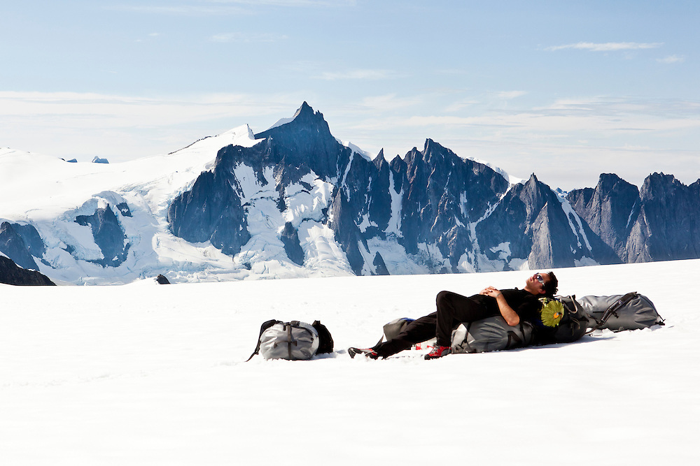 Colin Haley waiting for a heli pickup after completing the first ascent of the Devils Thumb traverse.