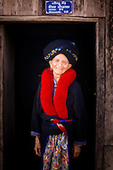 Laos, a small village near Muang Sing. Yao woman at the door of her house.