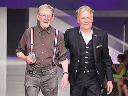 © Licensed to London News Pictures. 13/06/2012. London, England. Photographer Chris Moore receives a Lifetime Achievement Award from Jeff Banks. Gala Show and Awards Ceremony. Graduate Fashion Week 2012 at London's Earl's Court. Photo credit: Bettina Strenske/LNP