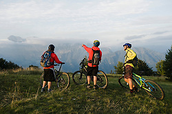 three mountain bikers looking at view, Kolovrat, Istria, Slovenia