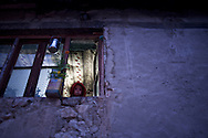 A child looks from the window of her family home, Kargil