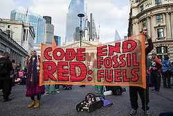London, UK. 2nd September, 2021. Extinction Rebellion climate activists hold a Code Red banner outside the Bank of England on the eleventh day of Impossible Rebellion protests. Extinction Rebellion are calling on the UK government to cease all new fossil fuel investment with immediate effect.