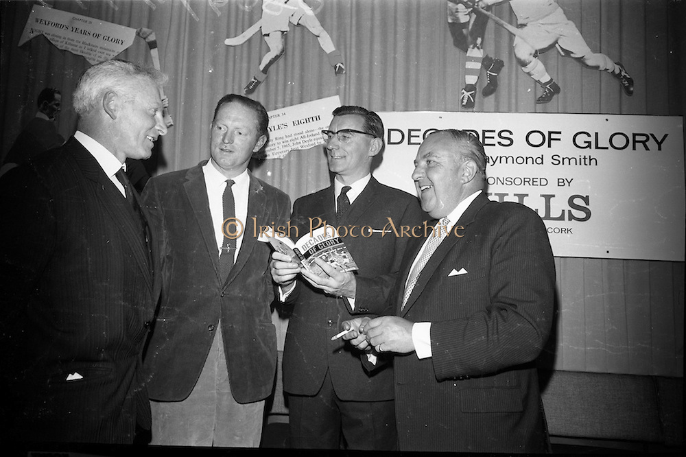 "17/05/1966<br /> 05/17/1966<br /> 17 May 1966<br /> Book reception for ""Decades of Glory: A Comprehensive History of the National Game"" by Raymond Smith.<br /> This reception was held in the offices of W.D. & H.O. Wills to honour the well known author and journalist, Raymond Smith. His book on the history of Hurling (""Decades of Glory"") has just been published with the assistance of Wills of Dublin and Cork and the Central Council of the G.A.A.<br /> Picture shows (from left to right): Sean Duggan (Galway), Billy Rackard (Wexford),  Raymond Smith (author), and Mr. Westropp Irvine (Factory Manager for W.D. & H.O. Wills, Dublin and son of late Mr. and Mrs. Tom Irvine, former manager of Provincial Bank, Wexford)."