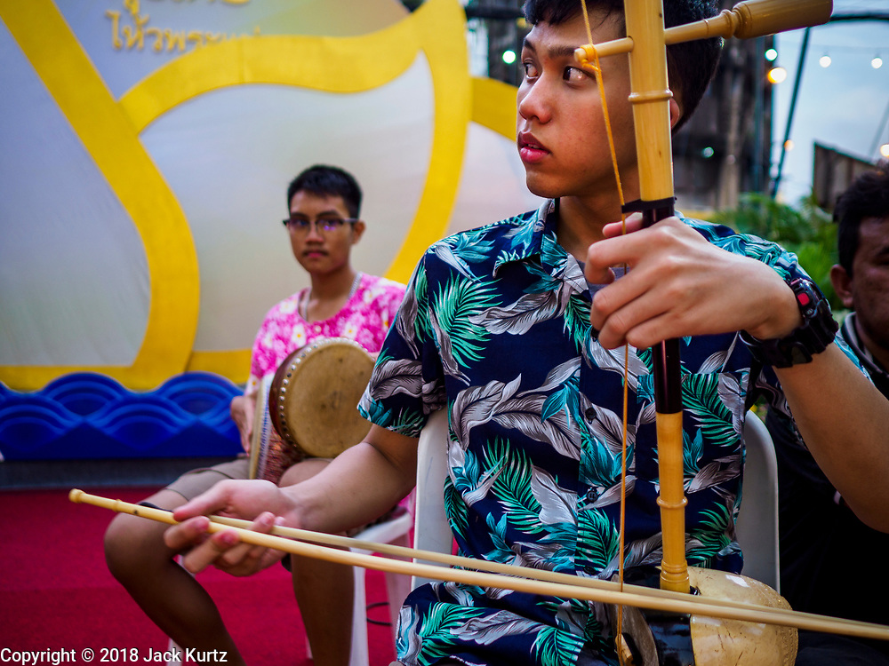 19 NOVEMBER 2018 - BANGKOK, THAILAND: A traditional Thai folk group performs during the Loy Krathong Fair along Klong (Canal) Ong Ang in Bangkok. This the first public event along the canal. Businesses that line the canal weve evicted about two years and the walkways along the canal were renovated. Loy Krathong takes place on the evening of the full moon of the 12th month in the traditional Thai lunar calendar. In the western calendar this usually falls in November. Loy means 'to float', while krathong refers to the usually lotus-shaped container which floats on the water. Traditional krathongs are made of the layers of the trunk of a banana tree or a spider lily plant. Now, many people use krathongs of baked bread which disintegrate in the water and feed the fish. A krathong is decorated with elaborately folded banana leaves, incense sticks, and a candle. A small coin is sometimes included as an offering to the river spirits. On the night of the full moon, Thais launch their krathong on a river, canal or a pond, making a wish as they do so. The krathongs made at the Klong Ong Ang fair were made out of bread so they would decompose and feed the fish in the canal. Loy Krathong will be celebrated on November 22 this year.     PHOTO BY JACK KURTZ