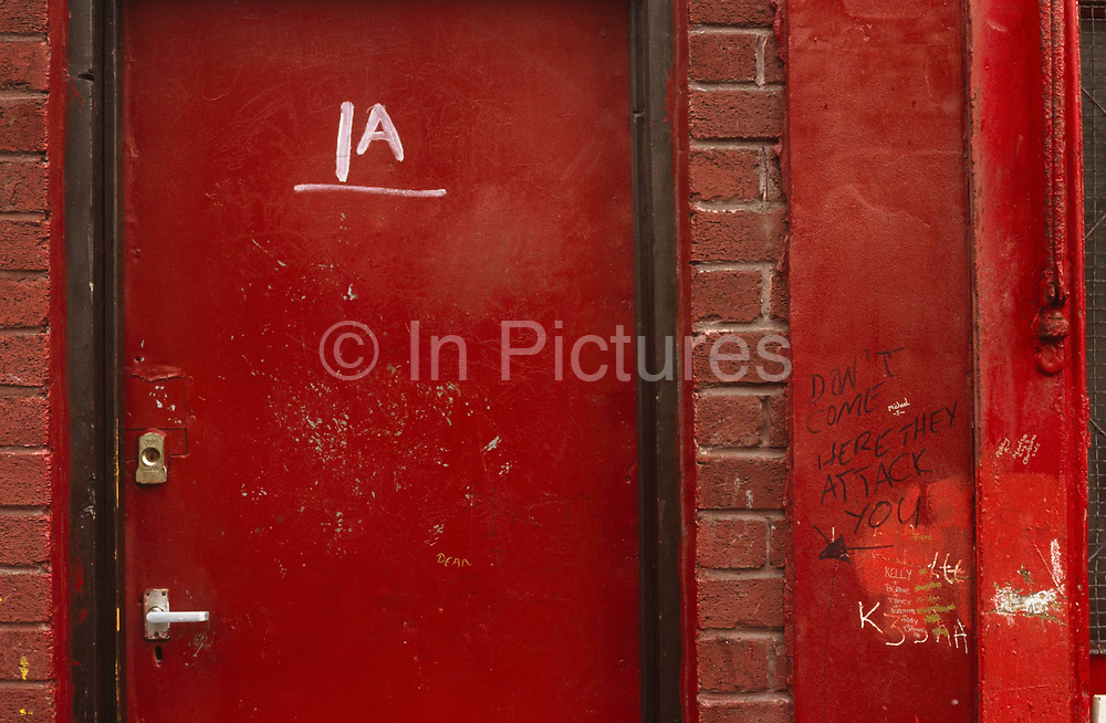 """The message in graffiti lettering """"Don't come here they attack you"""" has been written on a wall outside a house in the Toxteth area of Liverpool, Merseyside England. Flat 1A has a bright red-painted door and red bricks in an otherwise poverty-stricken district of this poor inner-city where crime and social deprivation has become the normal way of life for Scouses (someone from Liverpool). We see the red theme carried throughout this image of threat and ill-discipline where survival is clearly hard. These 'back to back' terraced houses have largely been demolished during Liverpool's regeneration during the 60s and 70s though some remain, accommodating unfortunate families on low-income."""