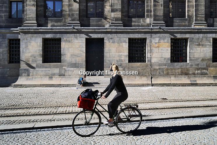 Nederland, Amsterdam, 16-5-2020 De regering laat het normale dagelijks leven weer langzaam opstarten . Door de afwezigheid van toeristen is het ongewoon rustig in de binnenstad van Amsterdam en is de stad te zien zoals jaren geleden was . geschiedenis, typisch,amsterdams,iconisch,historische,bebouwing,architectuur . massatoerisme,toeristisch, toeristische,toerisme,amsterdamse , historische, Een fietser passeert in de paleisstraat. Foto: Flip Franssen