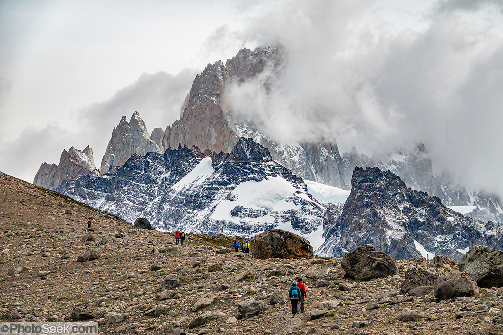 "Clouds swirl around Cerro Fitz Roy (3405 m or 11,171 ft elevation) seen from the trail ""Loma del Pliegue Tumbado"" near El Chalten,  in Los Glaciares National Park, Santa Cruz Province, Argentina, Patagonia, South America. From El Chalten, we hiked to Mirador ""Loma del Pliegue Tumbado"" (""hill of the collapsed fold"") 19 km (11.9 mi) with 1170 meters (3860 ft) cumulative gain. El Chalten mountain resort is 220 km north of El Calafate. Chaltén comes from a Tehuelche word meaning ""smoking mountain"", due to clouds that usually form over Monte Fitz Roy. Los Glaciares National Park and Reserve are honored on UNESCO's World Heritage List."